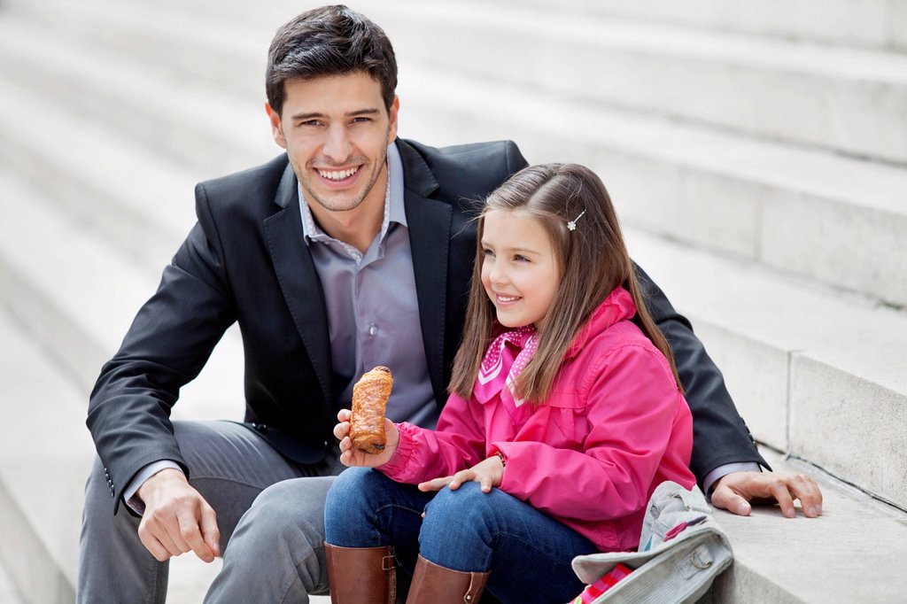 Man sitting with his daughter eating pain au chocolat : Stock Photo