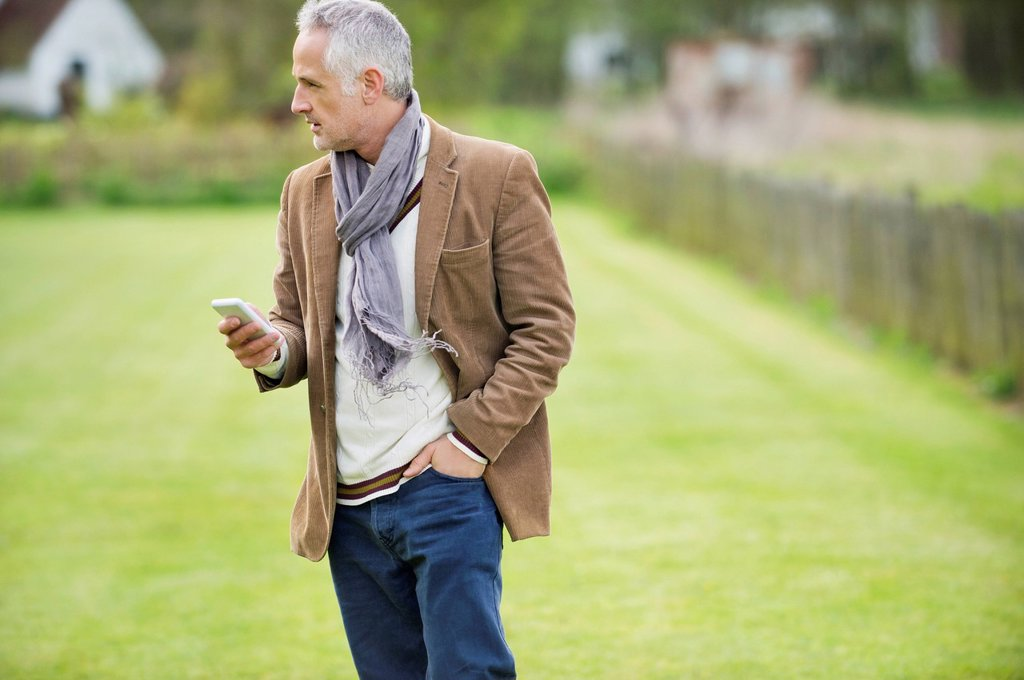 Stock Photo: 1738R-26745 Man text messaging on a mobile phone in a lawn