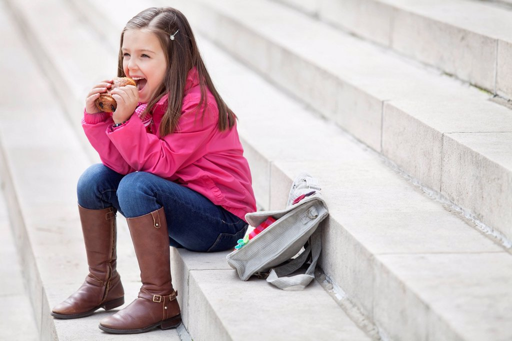 Schoolgirl sitting on the steps and eating pain au chocolat : Stock Photo
