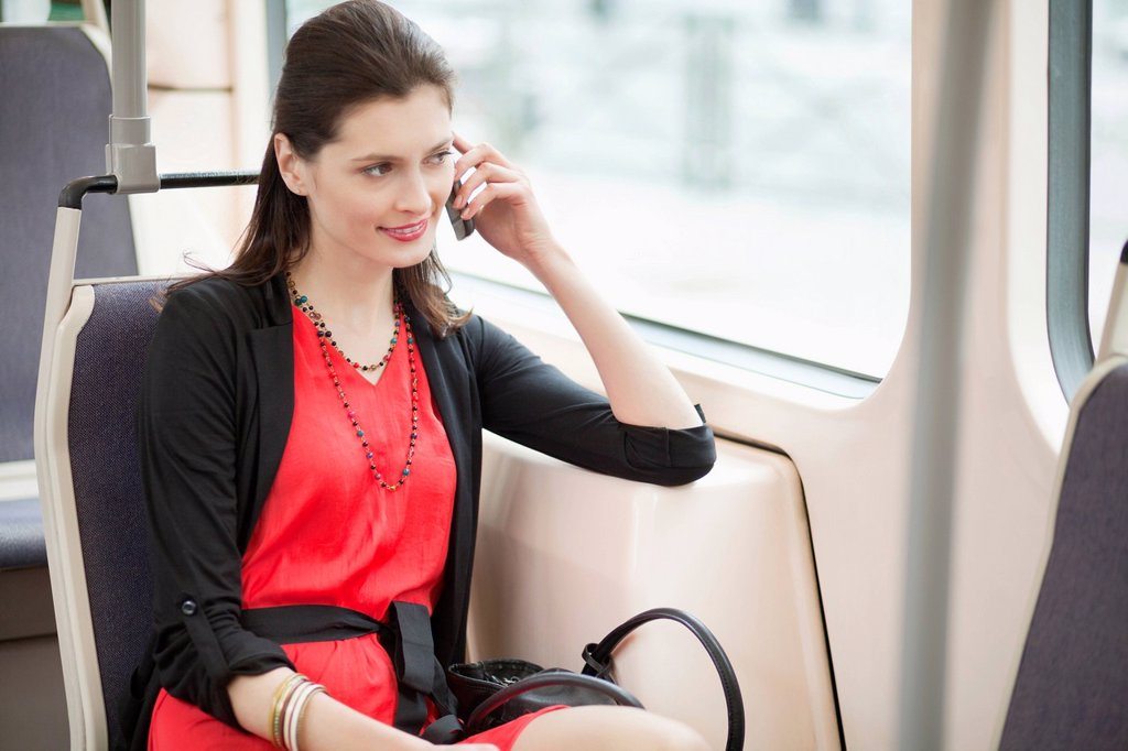Woman traveling in a tram and talking on a mobile phone : Stock Photo
