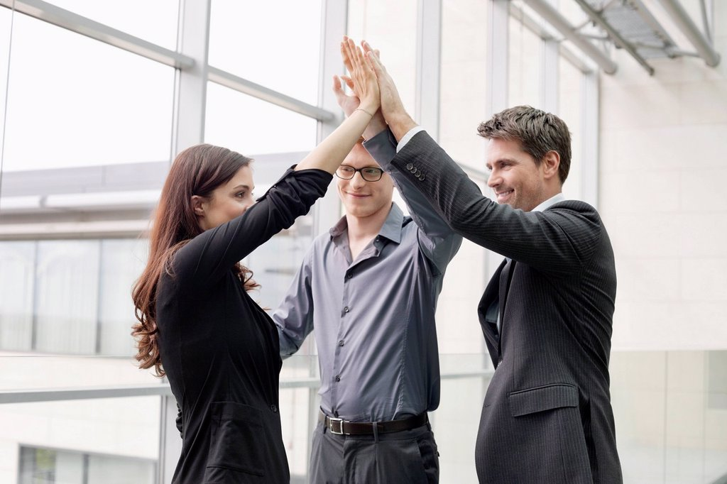 Business executives giving high_five to each other : Stock Photo