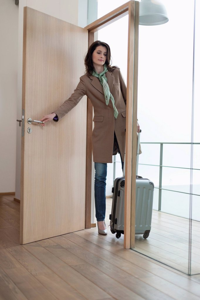Woman closing the door of a house : Stock Photo