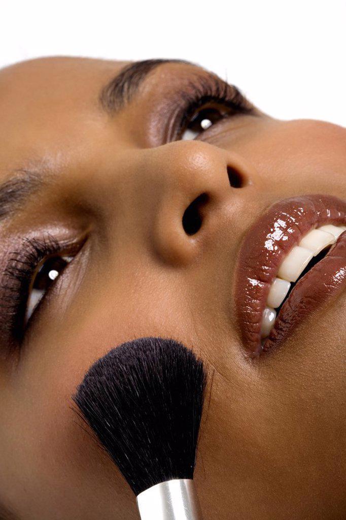 Young woman applying blush : Stock Photo