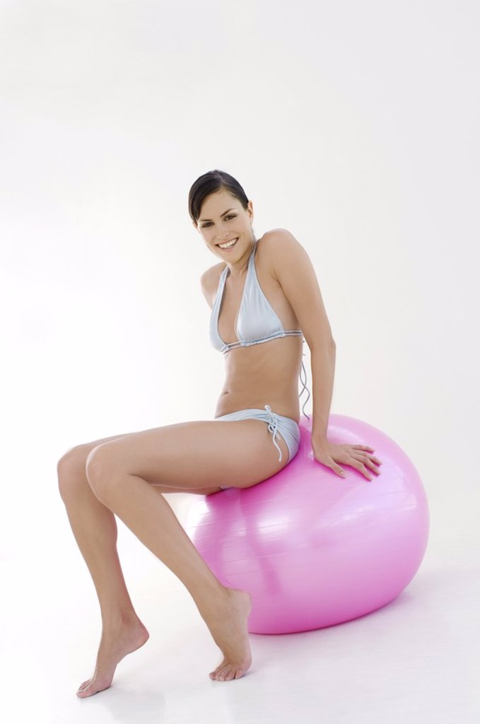 Stock Photo: 1738R-2885 Young smiling woman, sitting on big pink balloon