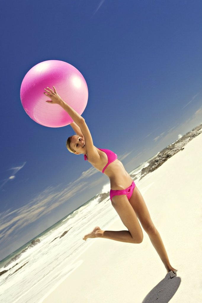 Stock Photo: 1738R-3016 Young smiling woman in pink bikini on the beach, lifting a large ball