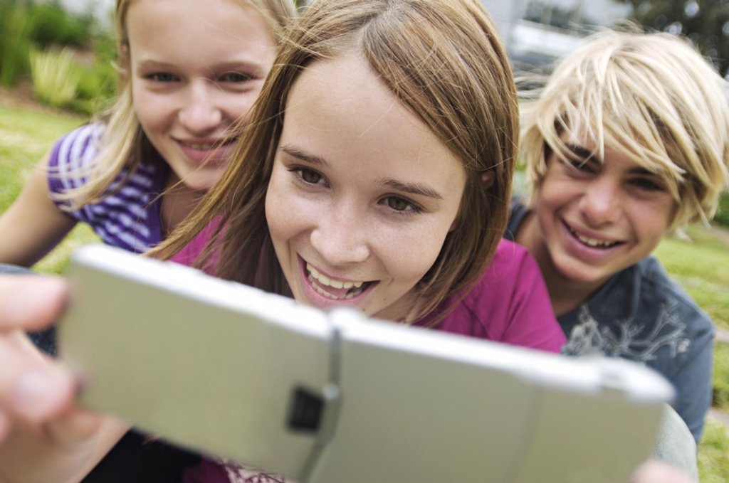 Stock Photo: 1738R-3145 2 smiling teenage girls and boy using camera phone, outdoors