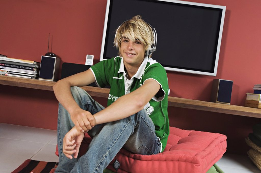 Teenage boy listening to music sitting in living-room : Stock Photo