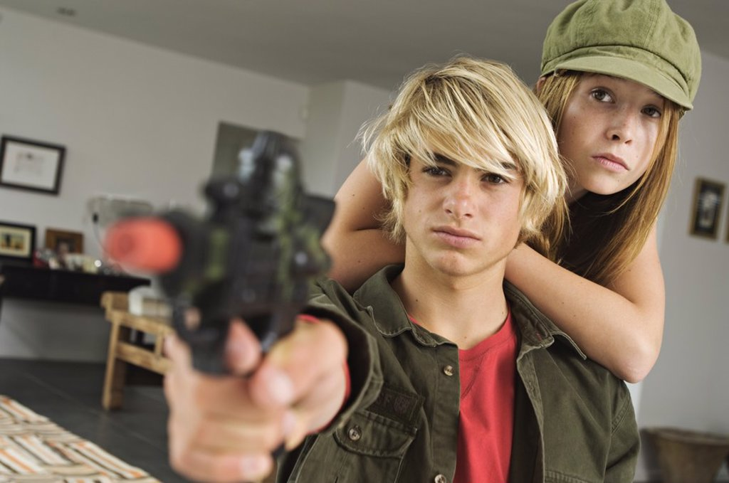 Teenage girl and boy aiming fake handgun : Stock Photo