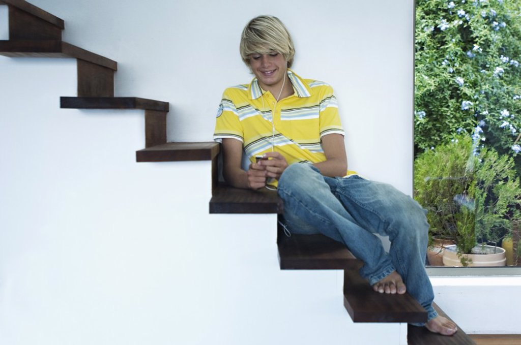 Teenage boy listening to music, sitting on stairs : Stock Photo