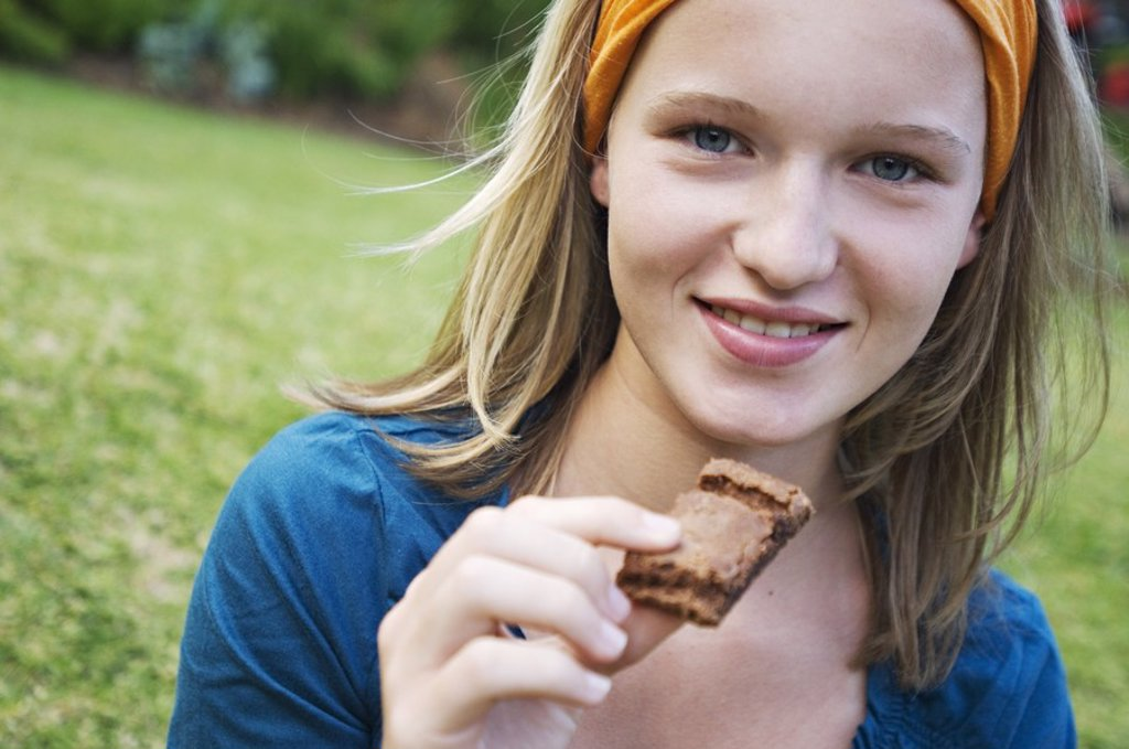 Portrait of a teenage girl holding piece of cake, outdoors : Stock Photo