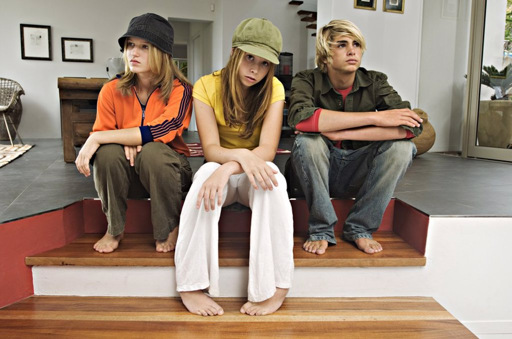 Stock Photo: 1738R-3152 2 teenage girls and 1 teenage boy looking sullen