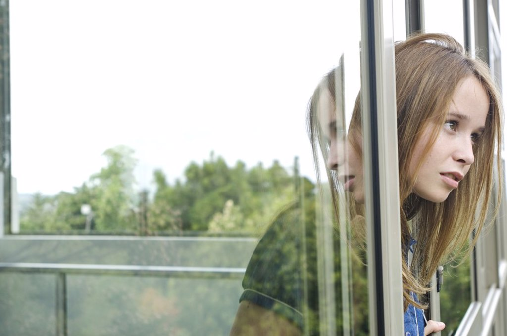 Thinking teenage girl at window : Stock Photo