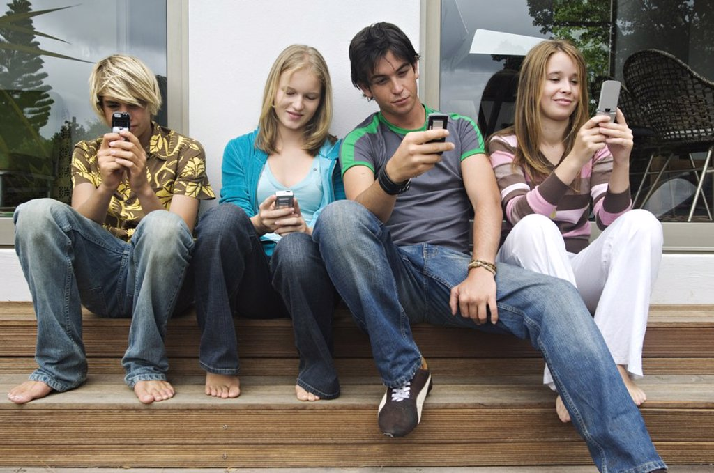 2 teenage boys and 2 teenage girls using their mobile phones : Stock Photo