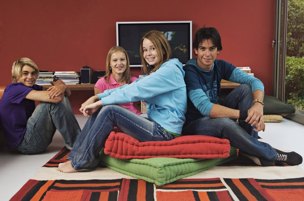 2 teenage girls and 2 teenage boys sitting in living-room : Stock Photo