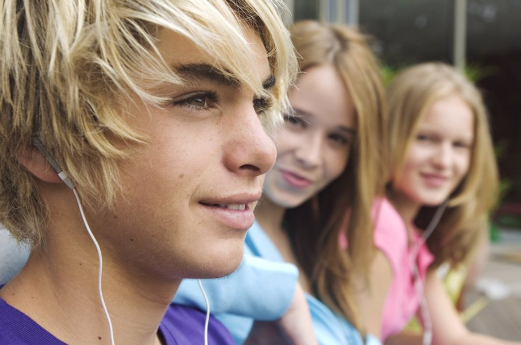 Portrait of teenage boy with earphones, 2 teenage girls in background : Stock Photo