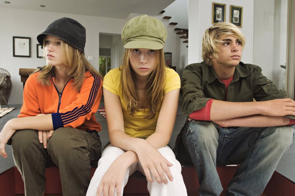 2 teenage girls and 1 teenage boy looking sullen : Stock Photo