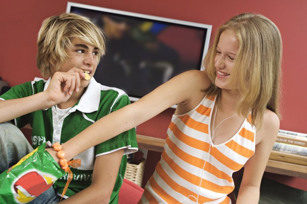 Teenage boy and girl eating crisps : Stock Photo