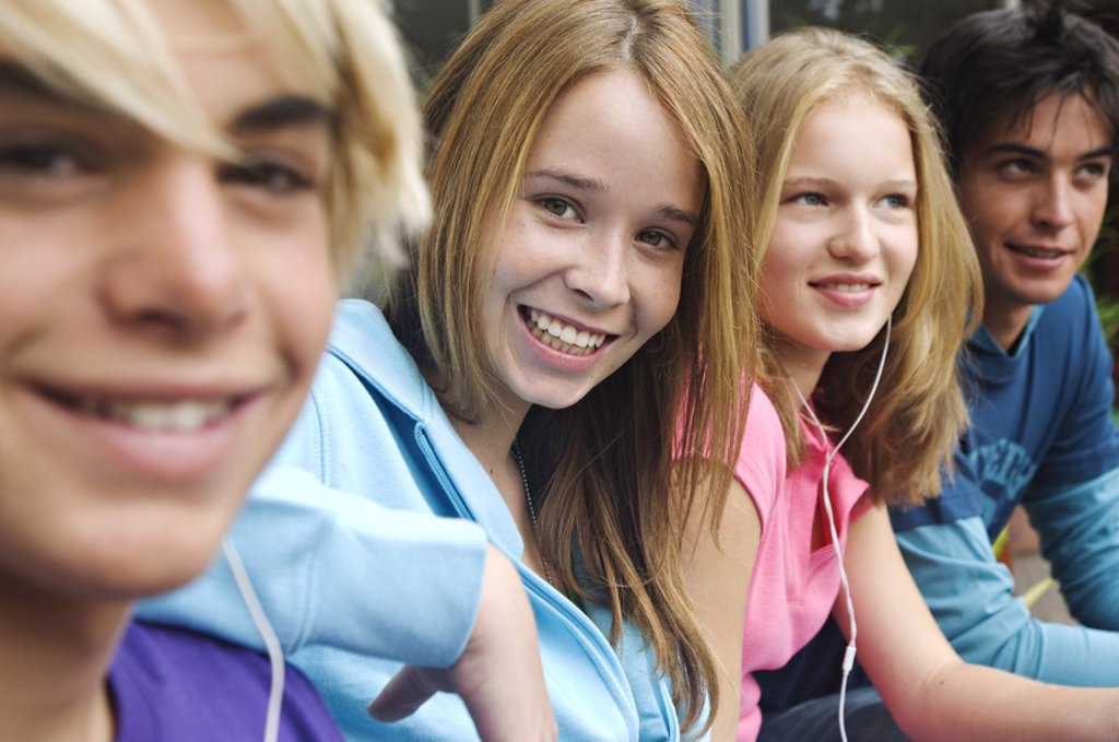 2 teenage boys and 2 teenage girls smiling for camera : Stock Photo