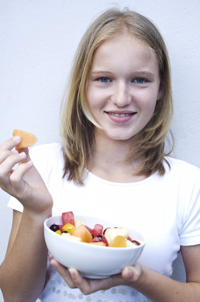 Stock Photo: 1738R-3169 Portrait of a teenage girl eating fruit salad