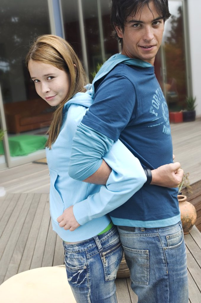 Teenage boy and girl embracing, back to back : Stock Photo