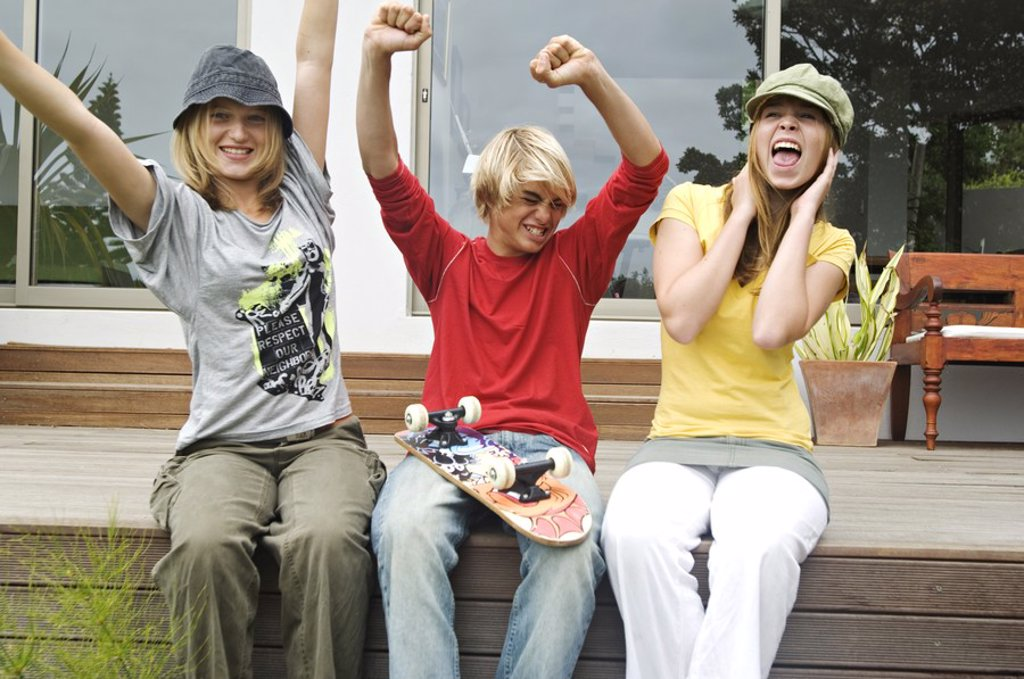 2 teenage girls and boy shouting, sitting on a terrace : Stock Photo