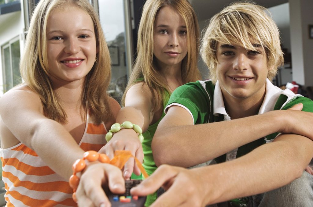 2 teenage girls and teenage boy using remote control : Stock Photo