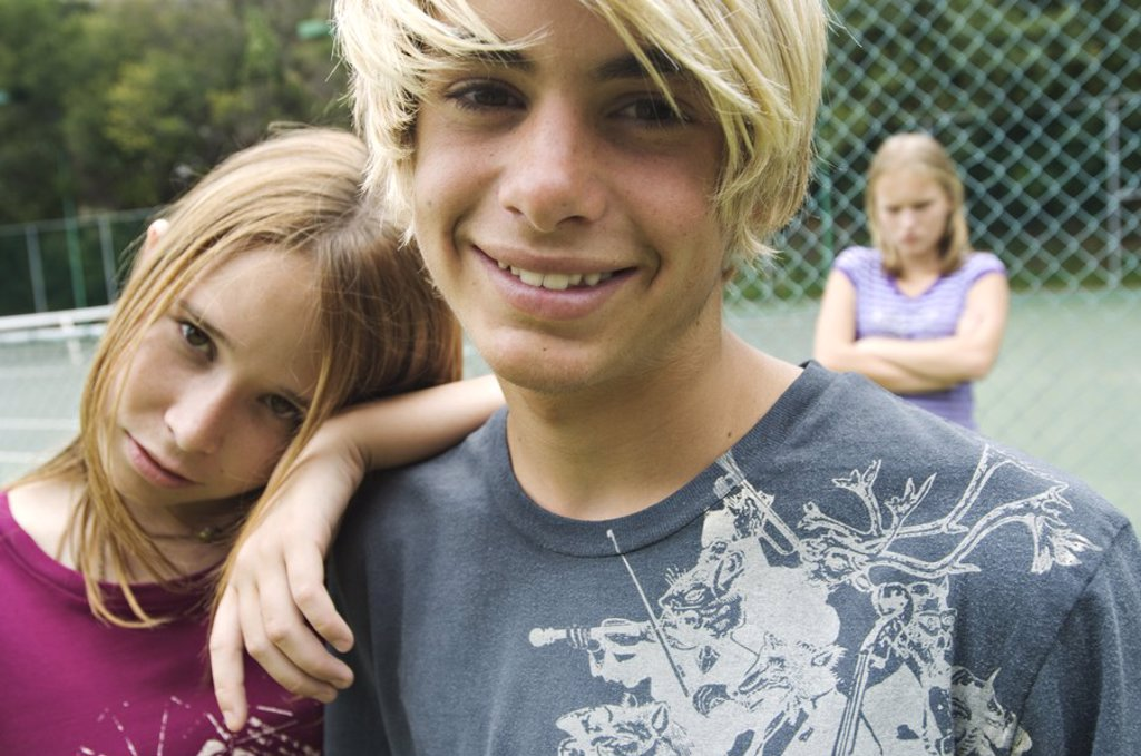 Smiling teenagers looking at the camera, teen girl with arms crossed in background, outdoors : Stock Photo