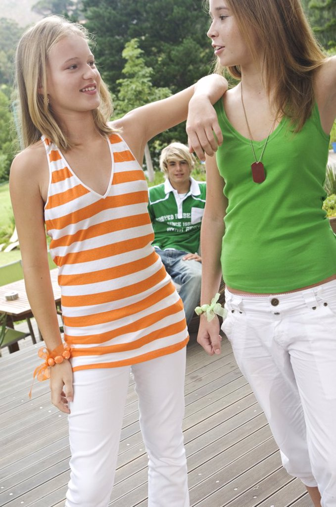 2 teenage girls looking at each other on a terrace, teenage boy sitting in background : Stock Photo