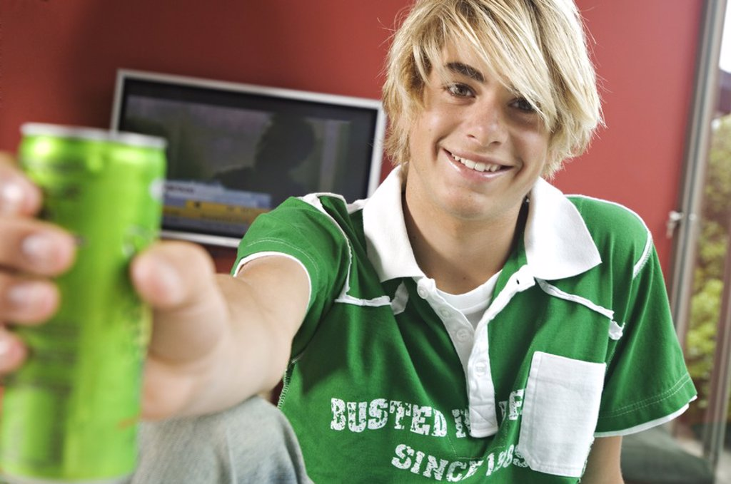 Stock Photo: 1738R-3184 Smiling teenage boy holding can