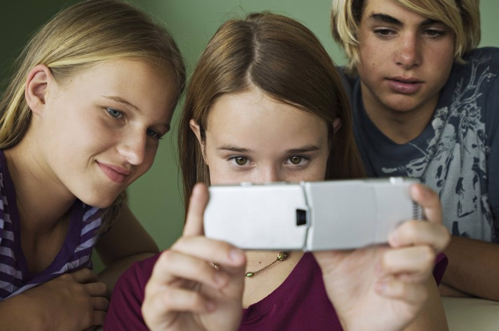 2 teenage girls and boy using camera phone : Stock Photo