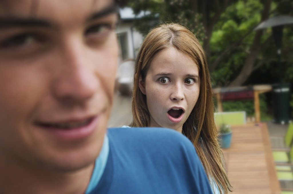 Surprised teenage girl with open mouth standing behind teenage boy : Stock Photo