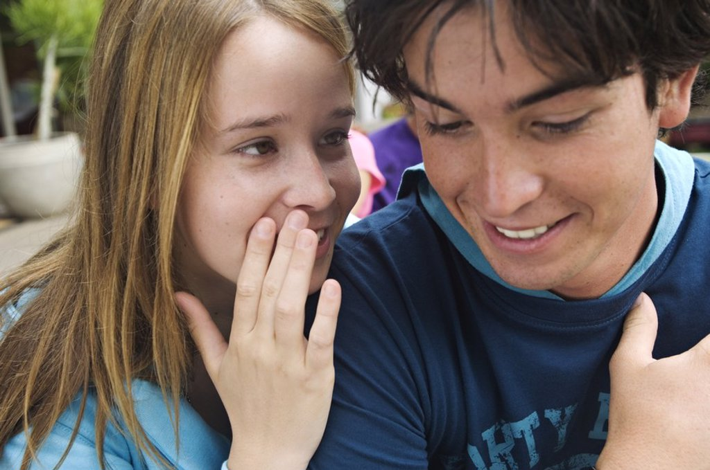 Teenage girl whispering secrets to teenage boy : Stock Photo