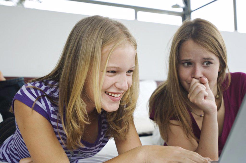 Stock Photo: 1738R-3204 2 smiling teenage girls lying on bed, using laptop