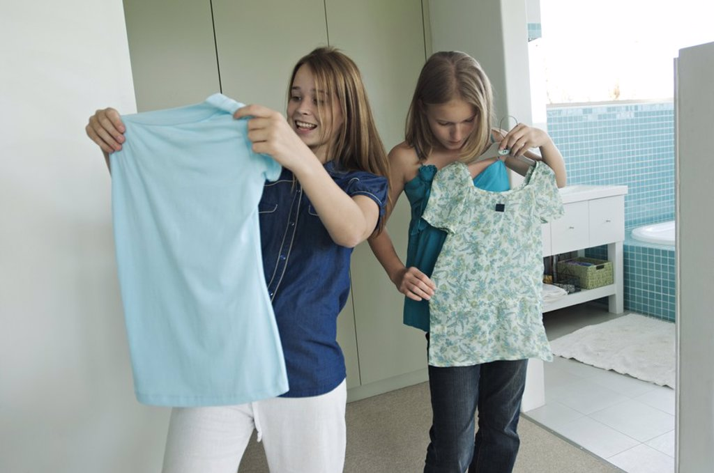 2 teenage girls trying on clothes : Stock Photo