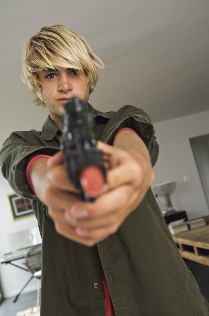 Teenage boy aiming handgun : Stock Photo