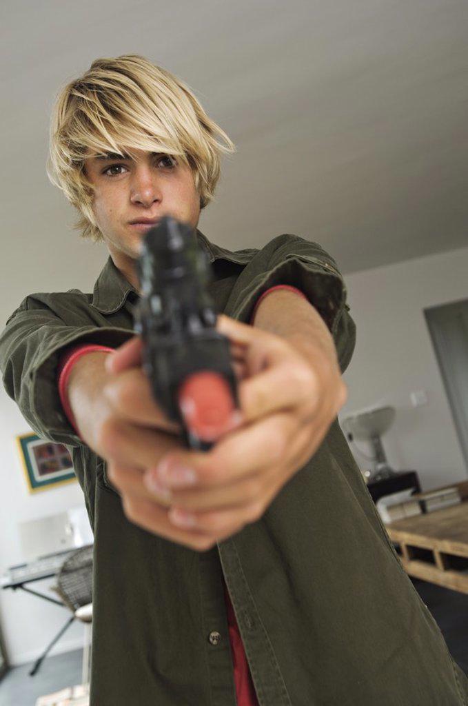 Stock Photo: 1738R-3208 Teenage boy aiming handgun