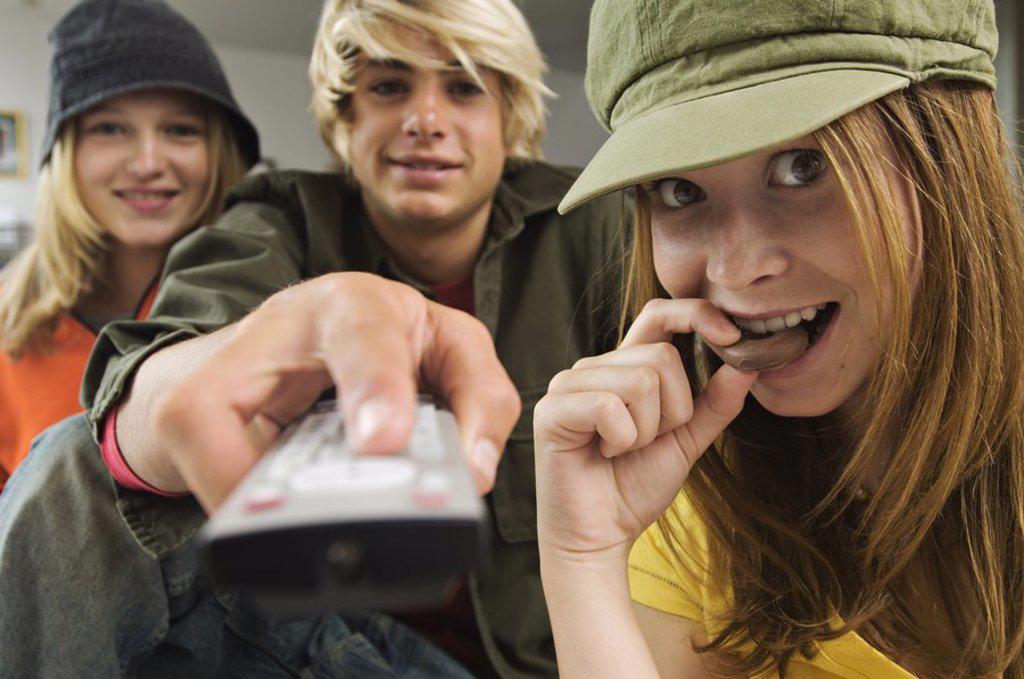 2 teenage girls and teenage boy using remote control : Stock Photo