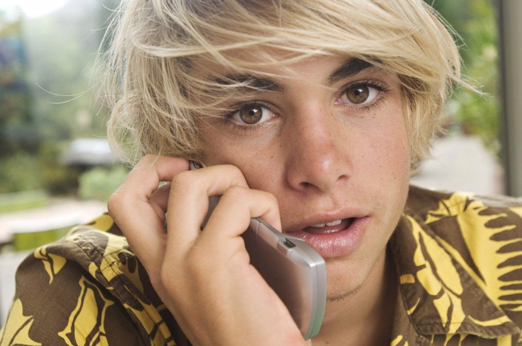 Stock Photo: 1738R-3213 Portrait of a teenage boy using mobile phone