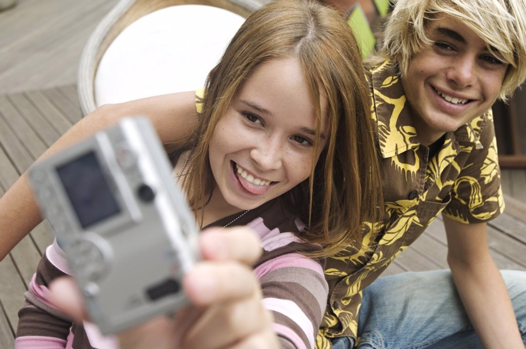 Teenage girl and boy photographing themselves : Stock Photo