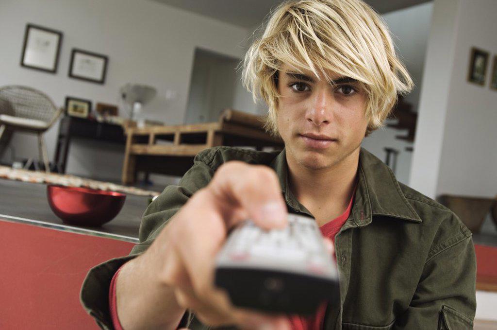 Teenage boy using remote-control : Stock Photo