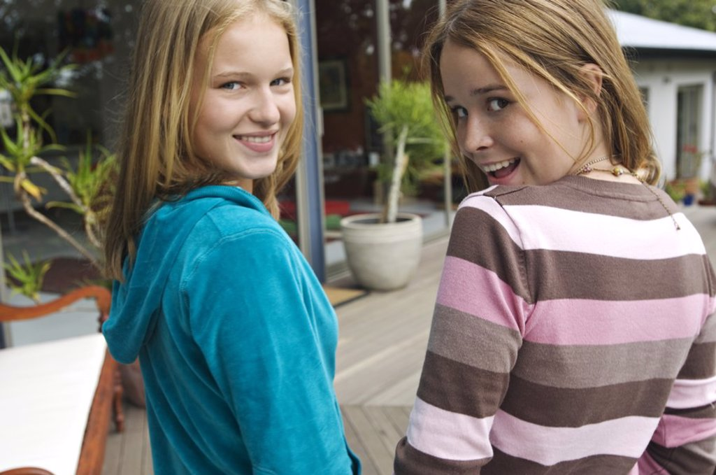 Stock Photo: 1738R-3223 2 smiling teenage girls looking over shoulders