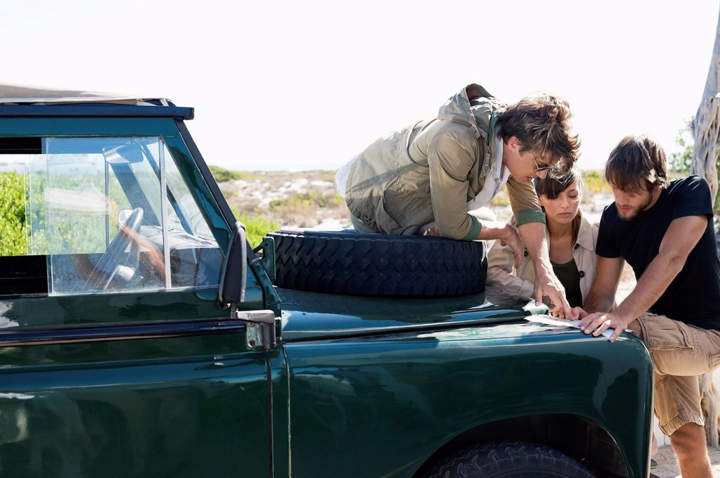 Stock Photo: 1738R-32673 Friends looking at map beside a SUV