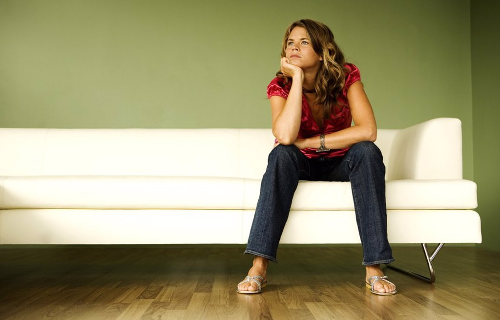 Young thinking woman sitting on a sofa : Stock Photo