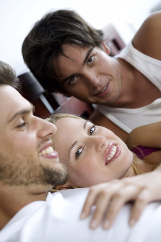 2 smiling men and a woman lying in bed : Stock Photo