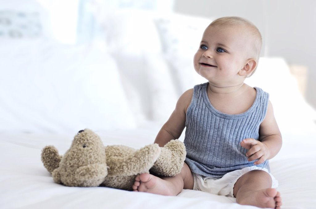 Baby sitting with teddy bear, indoors : Stock Photo