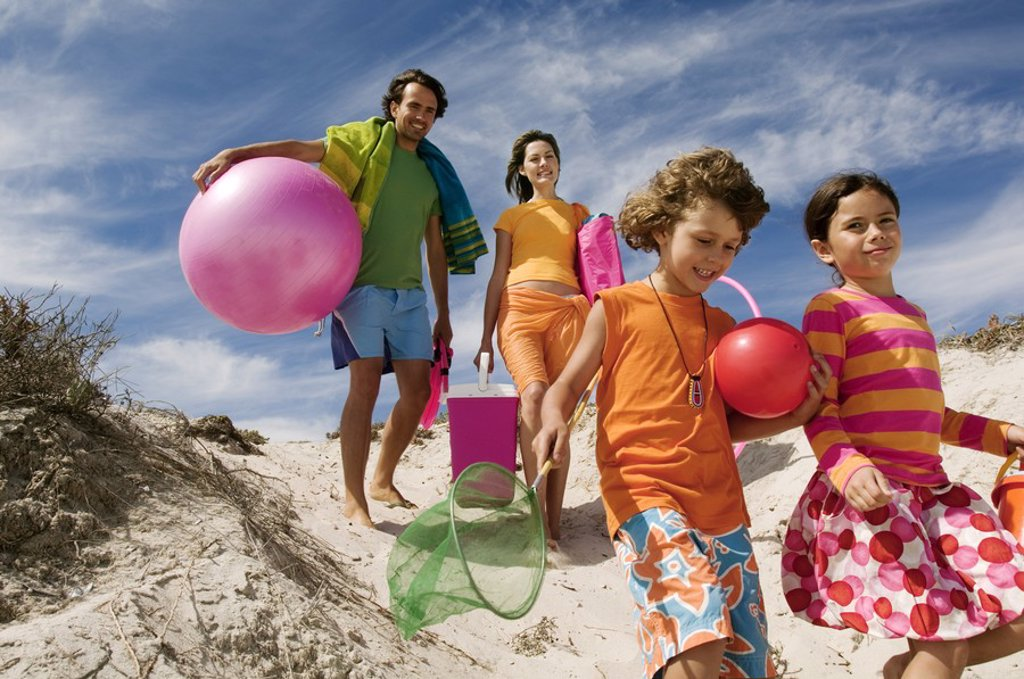 Stock Photo: 1738R-3523 Parents and two children walking on the beach, outdoors
