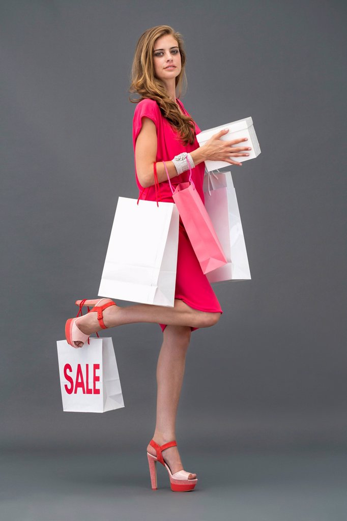Stock Photo: 1738R-35272 Portrait of a woman posing with shopping bags