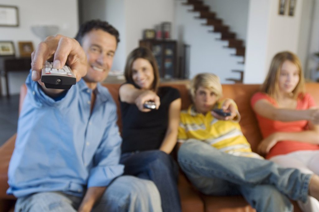 Stock Photo: 1738R-3718 Parents and two teens holding eachothers a remote control, indoors