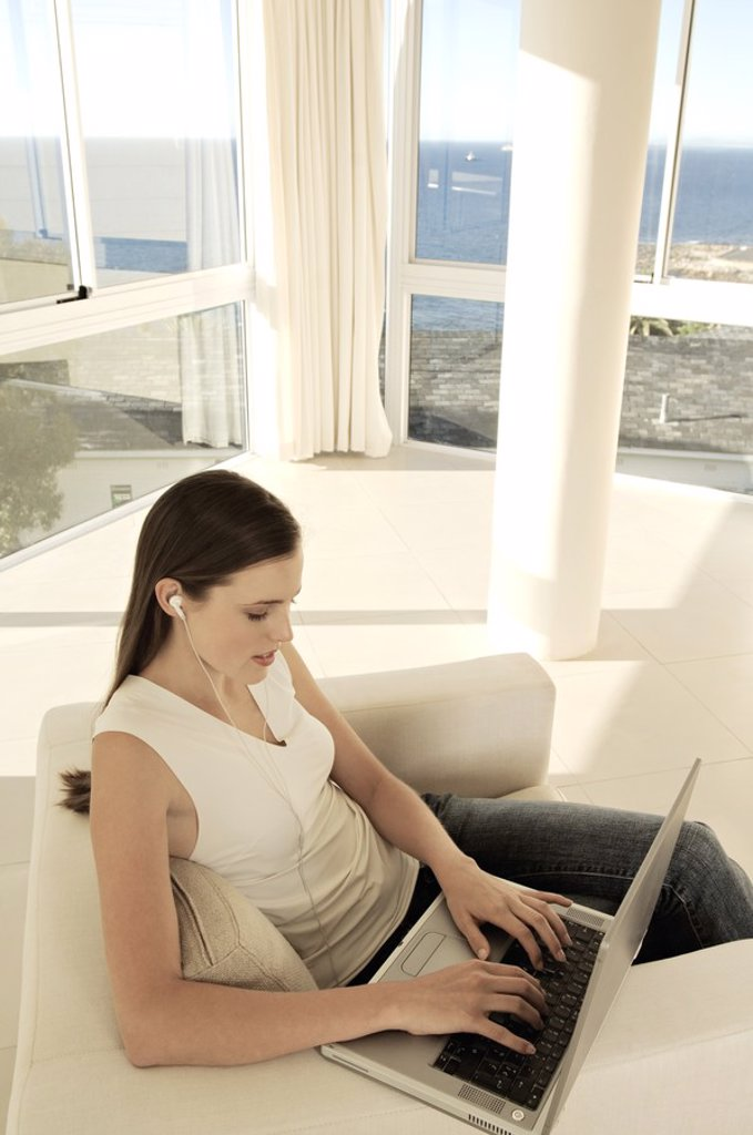 Young woman using laptop in living-room : Stock Photo