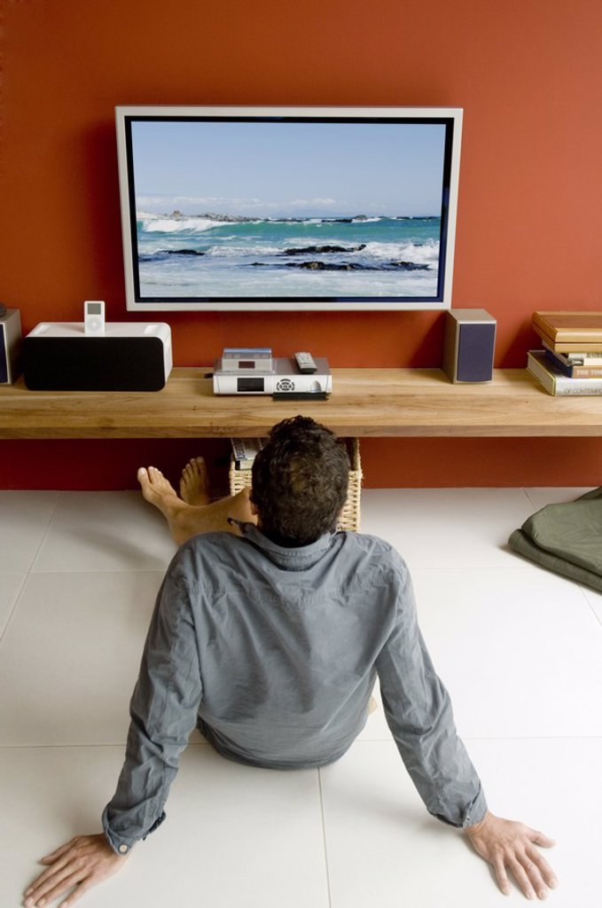 Stock Photo: 1738R-4064 Man watching TV sitting on floor